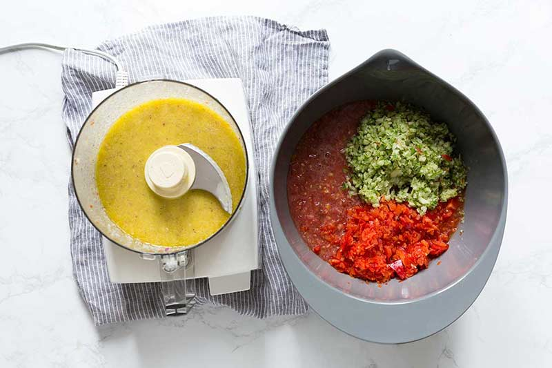 A large bowl full of assorted gazpacho ingredients next to a food processor filled with pureed olive oil, red onions and garlic.