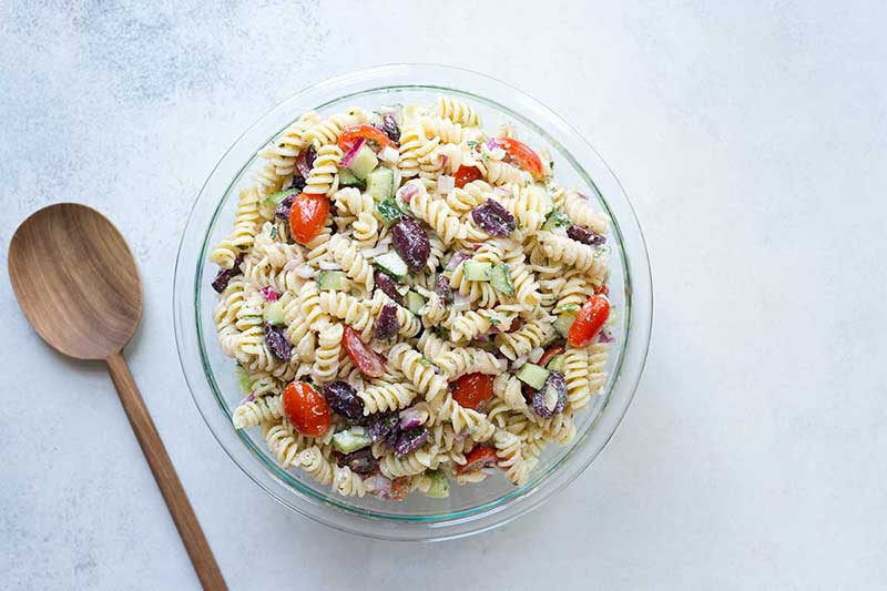 Summer rotini pasta salad in a bowl on a pale backdrop next to a wood spoon.