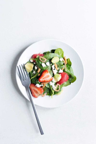 Overhead photo of a strawberry spinach salad recipe on a white plate with a silver fork.