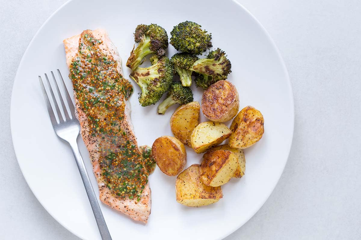 Baked salmon with potatoes and broccoli on a white plate, topped with a sauce made from whole grain mustard and chives.