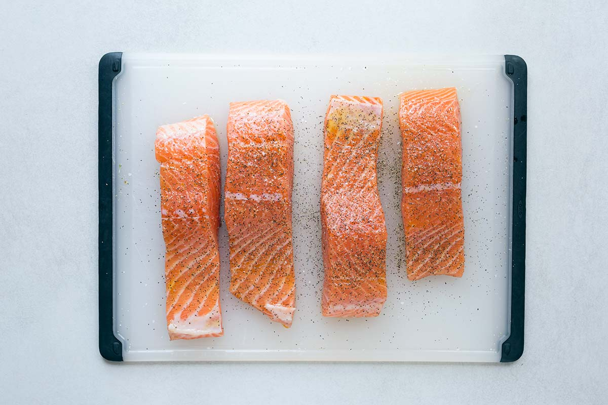 Four raw center-cut salmon fillets on a cutting board, seasoned with salt and pepper.