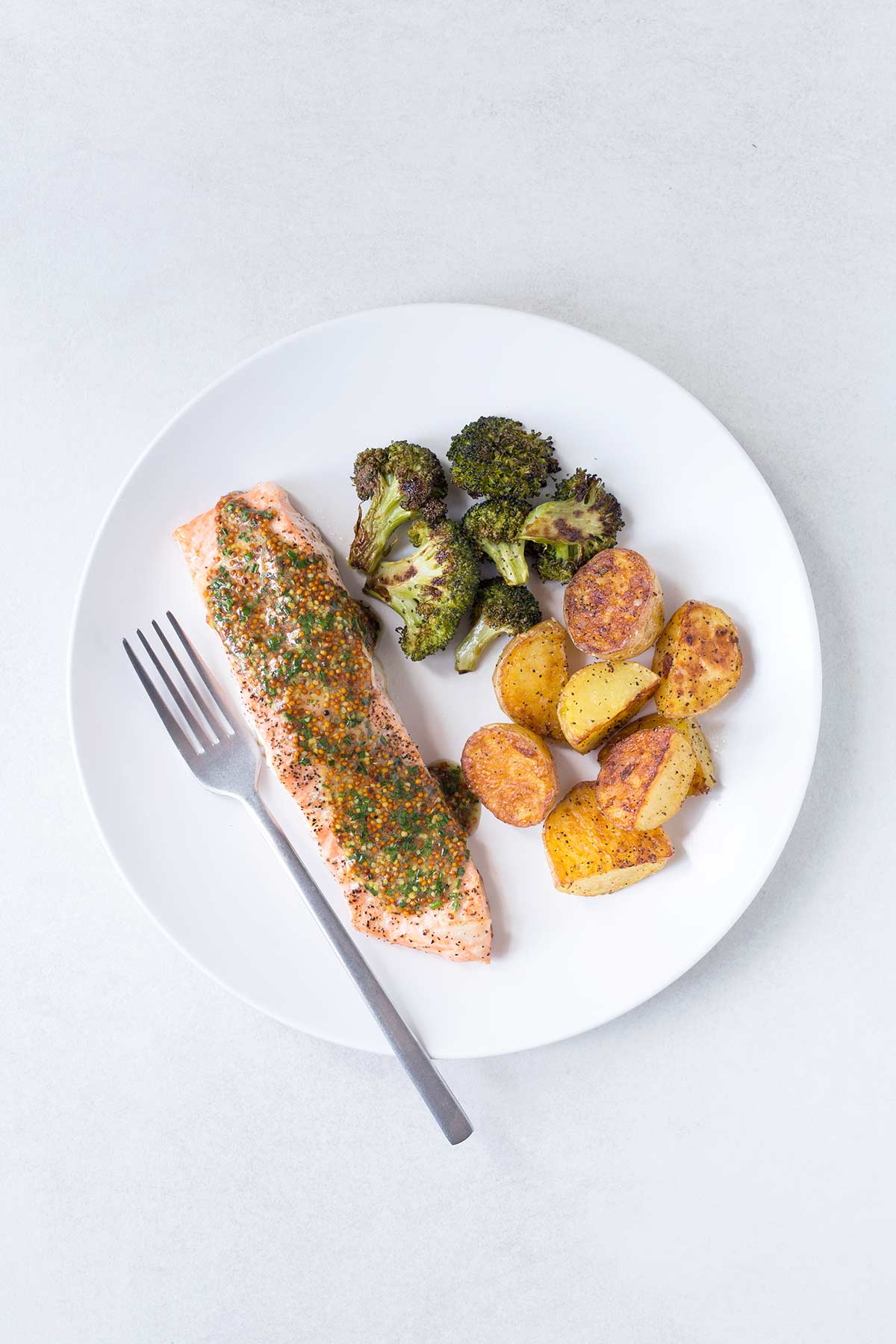 Roasted salmon, potatoes, and broccoli on a white plate with a fork, topped with a sauce.