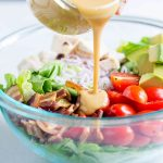 Honey Mustard Vinaigrette being poured over salad.