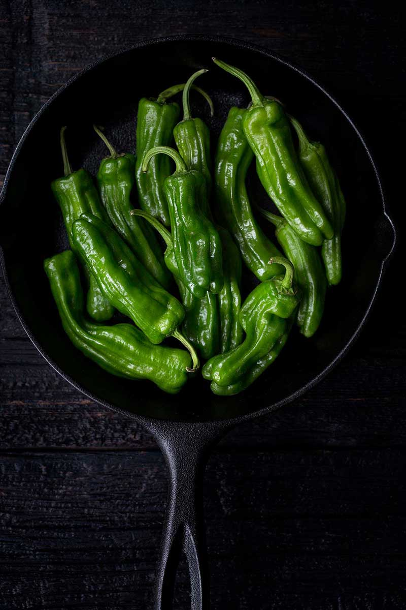 Fresh, uncooked shishito peppers in a cast iron skillet.