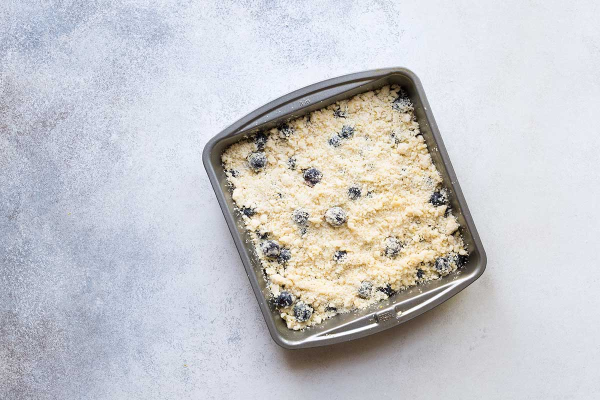 Blueberry crumble bar ingredients in an 8x8 inch pan.