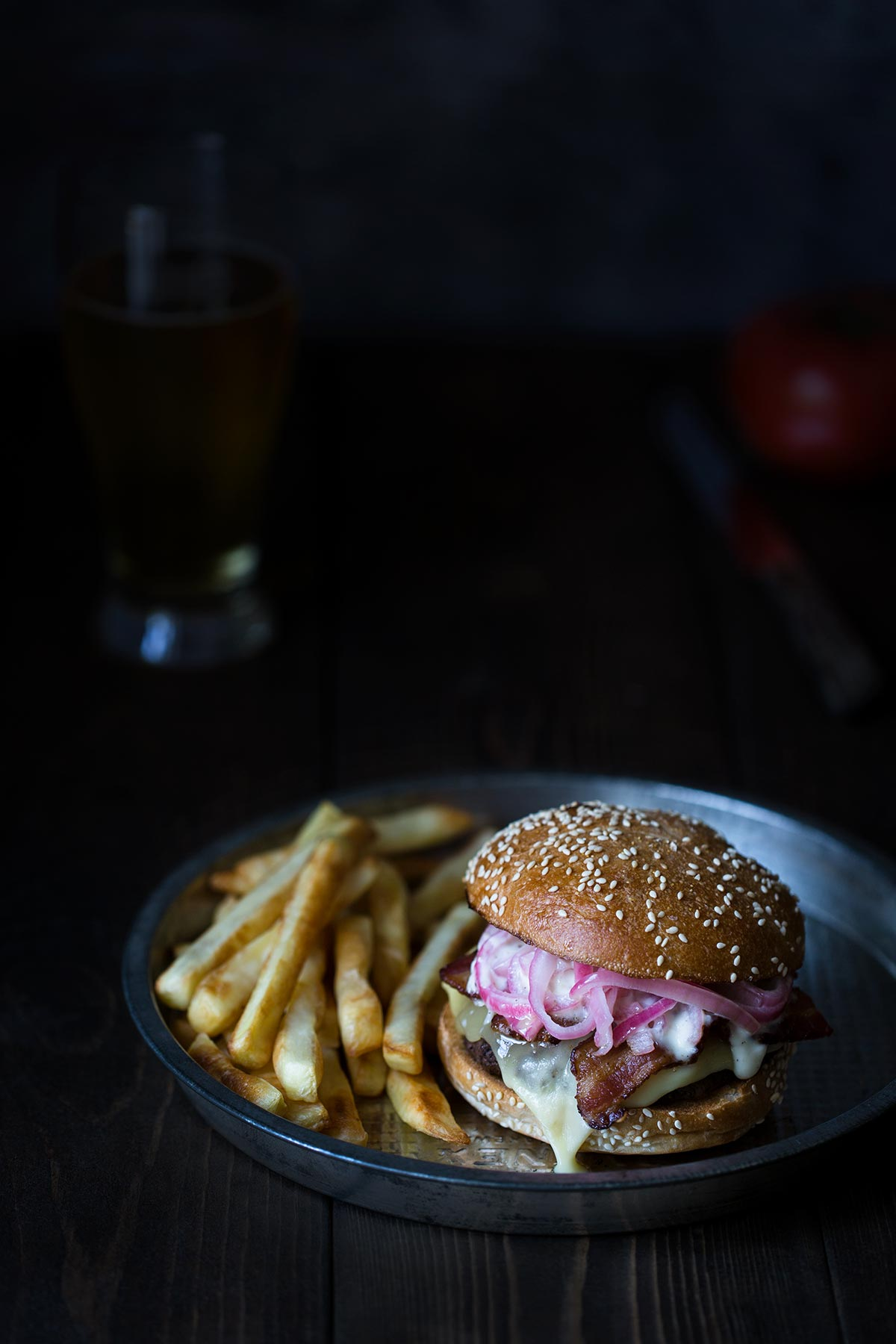 A raclette bacon cheeseburger topped with pickled shallots, horseradish aioli, served on a plate with french fries.