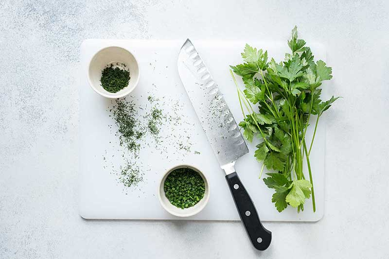 An overhead photo of a white cutting board, chef's knife, and fresh herbs (both chopped and whole).