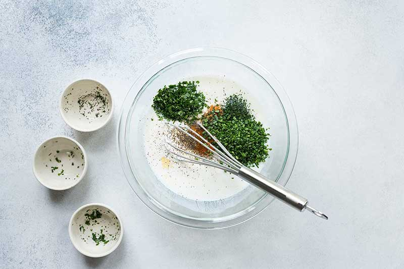 A mixing bowl filled with ingredients for buttermilk ranch dressing and a whisk.