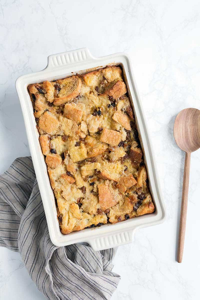 A bread pudding recipe in a white casserole dish, next to a wooden spoon.