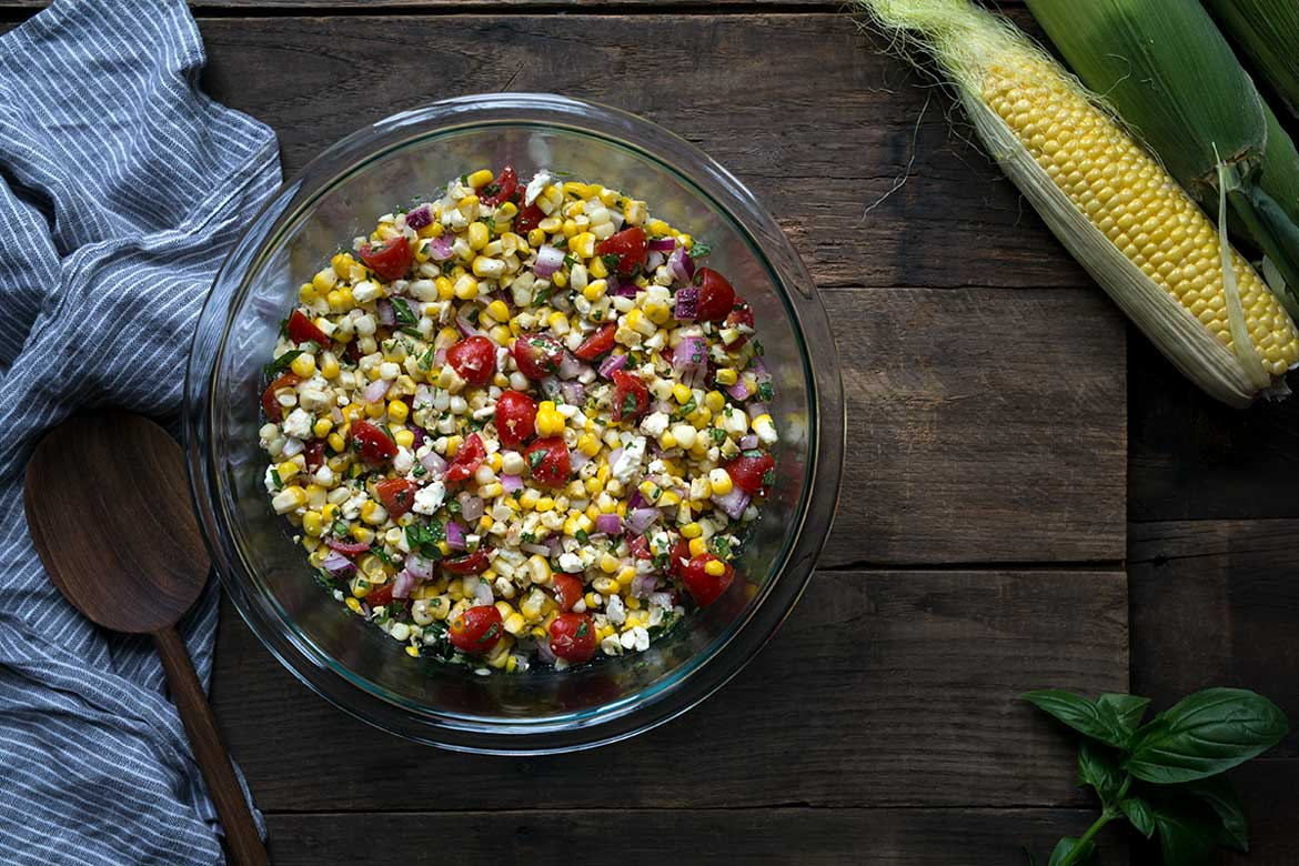 Photo of corn salad recipe in a bowl on a wood backdrop, surrounded by fresh corn and a blue napkin.