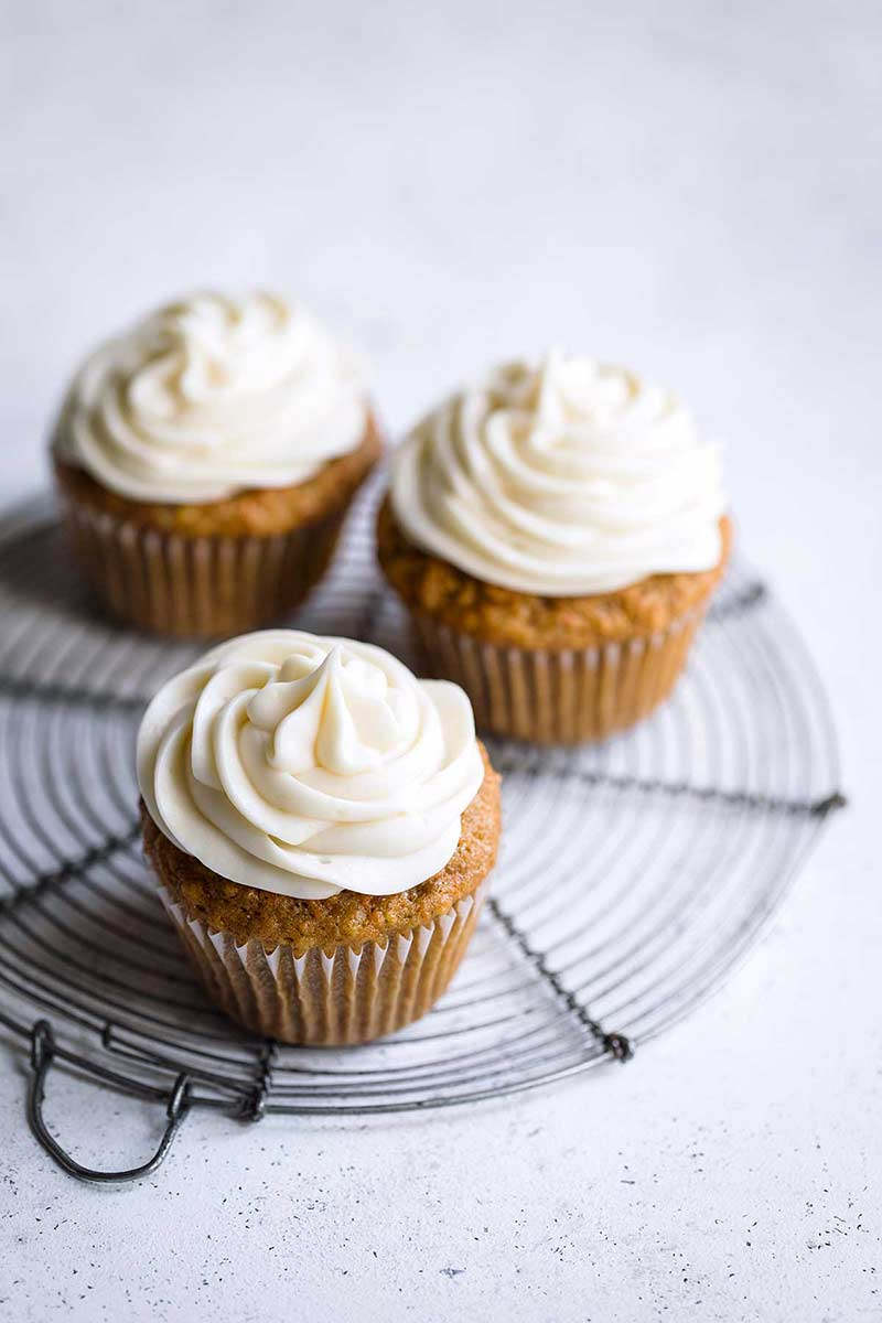 Closeup of three carrot cupcakes with cream cheese frosting
