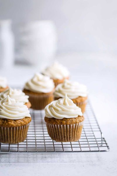 baked cupcakes topped with cream cheese frosting on a cooling rack