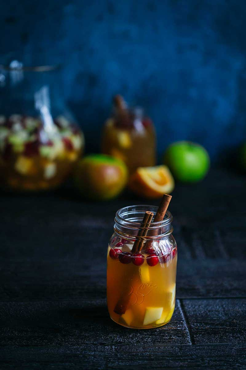 Homemade apple cider sangria in a mason jar, garnished with cinnamon sticks