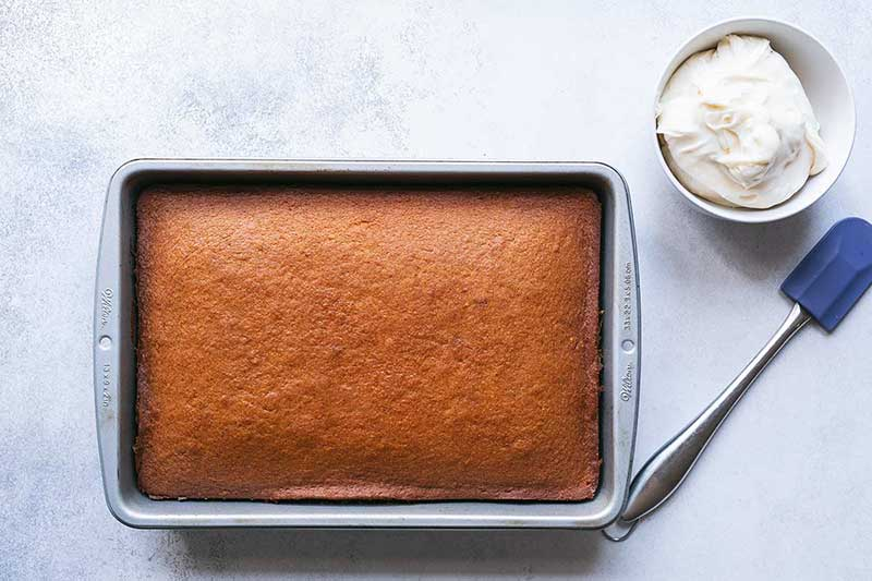 Unfrosted pumpkin cake in pan next to a bowl of cream cheese frosting