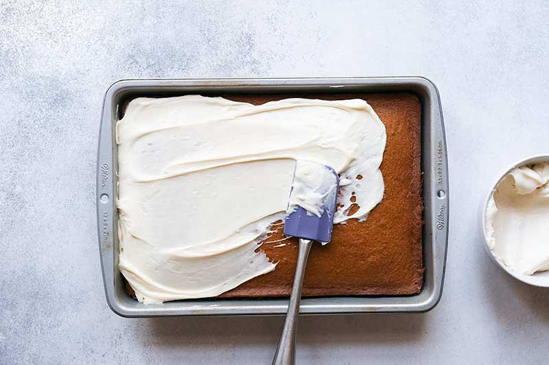 A spatula spreading cream cheese frosting over homemade pumpkin cake