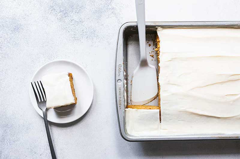 A slice of pumpkin cake next to the pan of cake.
