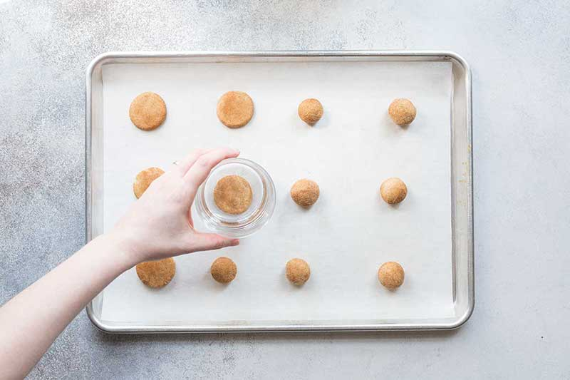 Raw snickerdoodles on a sheet pan, being flattened with a drinking glass.
