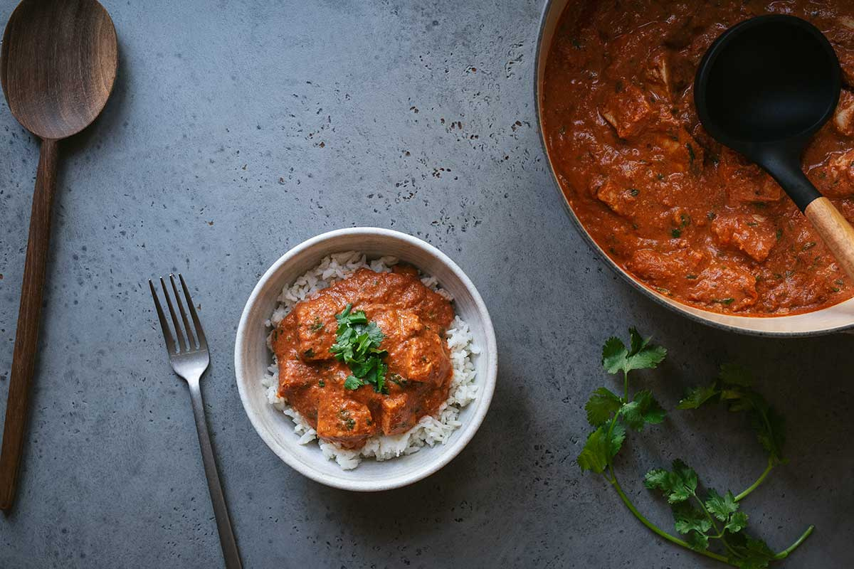 A bowl of chicken tikka masala on a blue backdrop