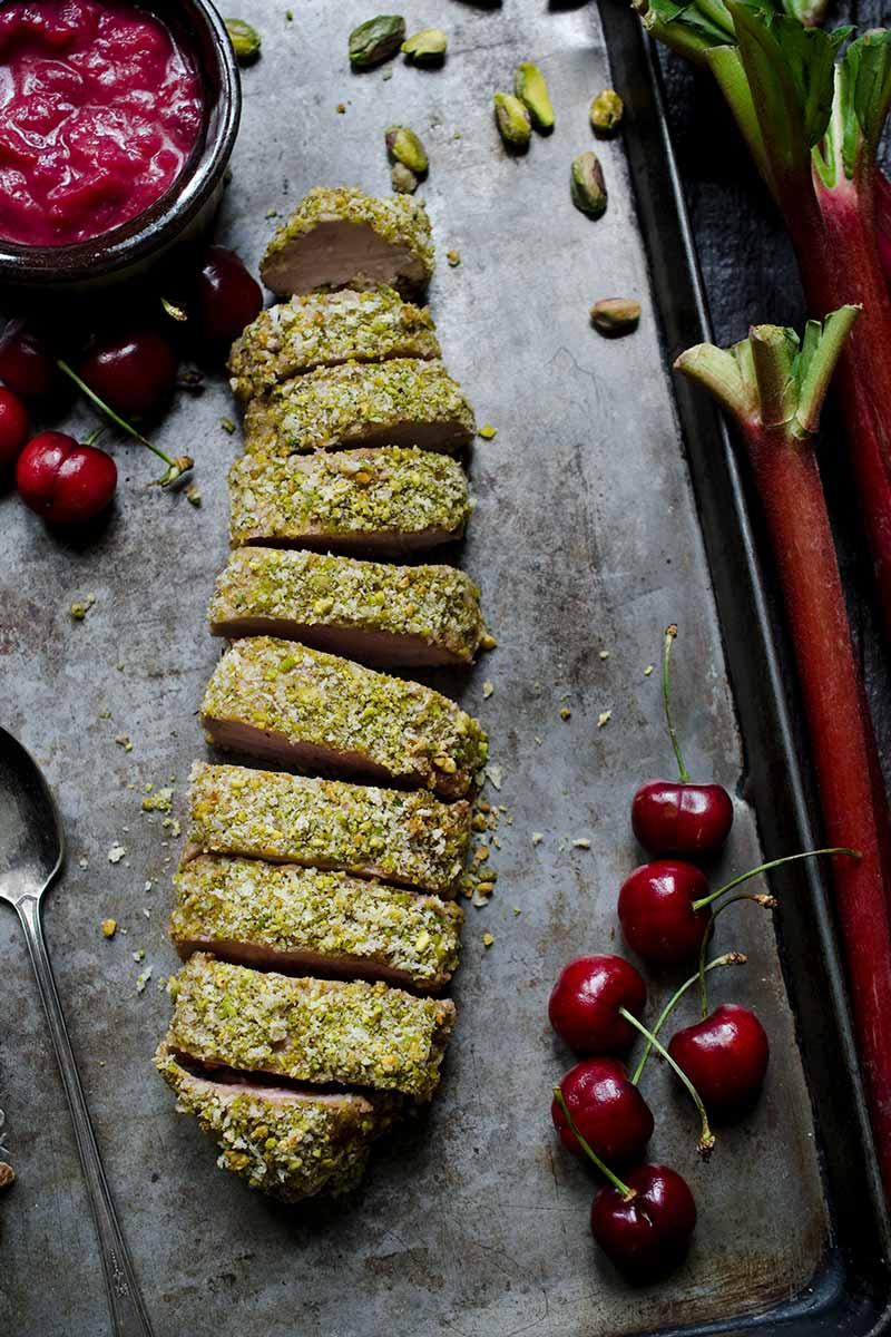 Pistachio crusted pork tenderloin surrounded by cherries