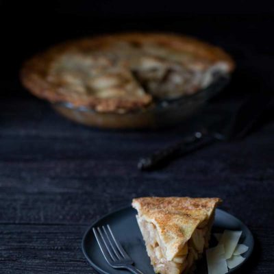 A slice of Classic Homemade Apple Pie on a plate, with the full apple pie recipe in the background
