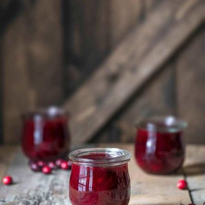 Homemade Cranberry Sauce Recipe in three mason jars, surrounded by scattered cranberries.