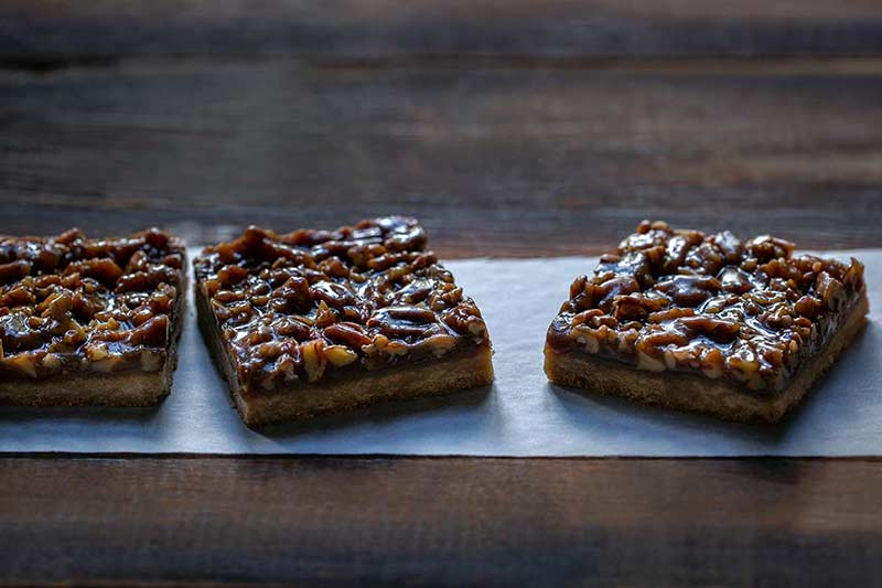 Three pecan pie bar slices on parchment