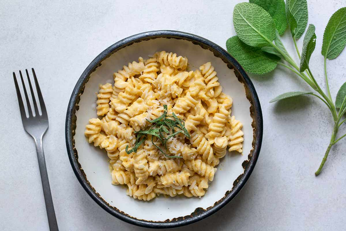 A bowl of butternut squash pasta topped with thinly sliced sage