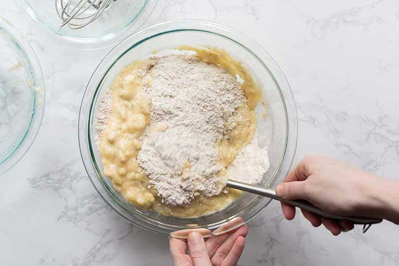Stirring banana bread muffin recipe ingredients in a bowl.