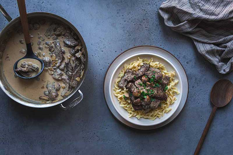 Beef stroganoff in a large flat-sided skillet with a ladle next to a bowl of the recipe served over noodles