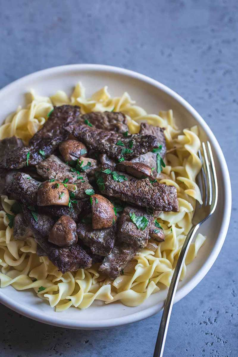 Closeup of beef stroganoff in a bowl, showcasing beed, mushrooms, and fresh parsley