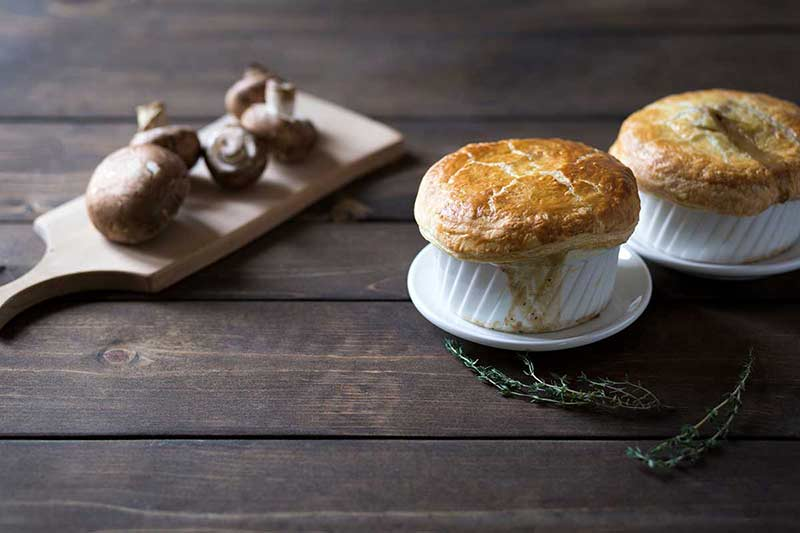Two single serving pot pies next to mushrooms