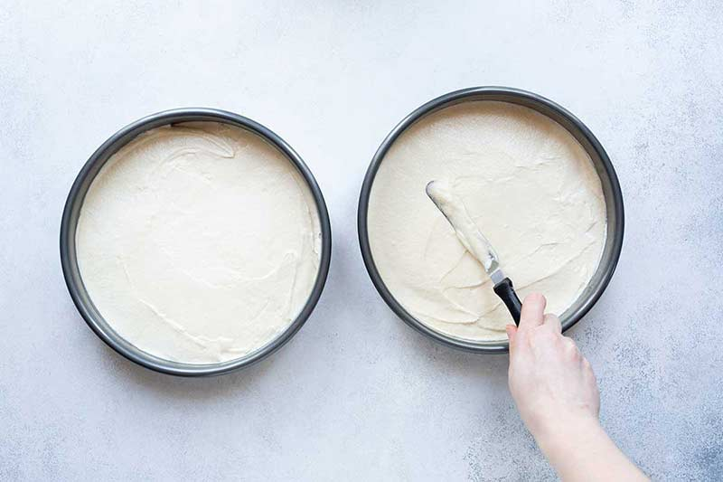 White cake batter being evenly distributed in pans with a spatula