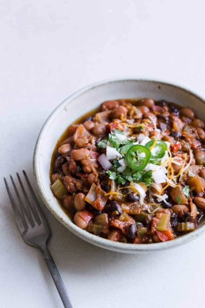 Closeup of homemade vegan chili recipe in a bowl, topped with sour cream. hot peppers and cheese