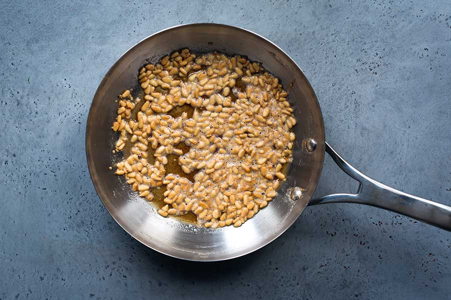Pine nuts cooked in butter in a skillet