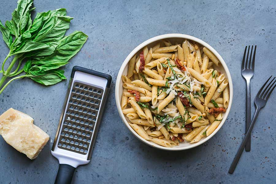 Sun-Dried Tomato Pesto Pasta surrounded by basil and parmesan
