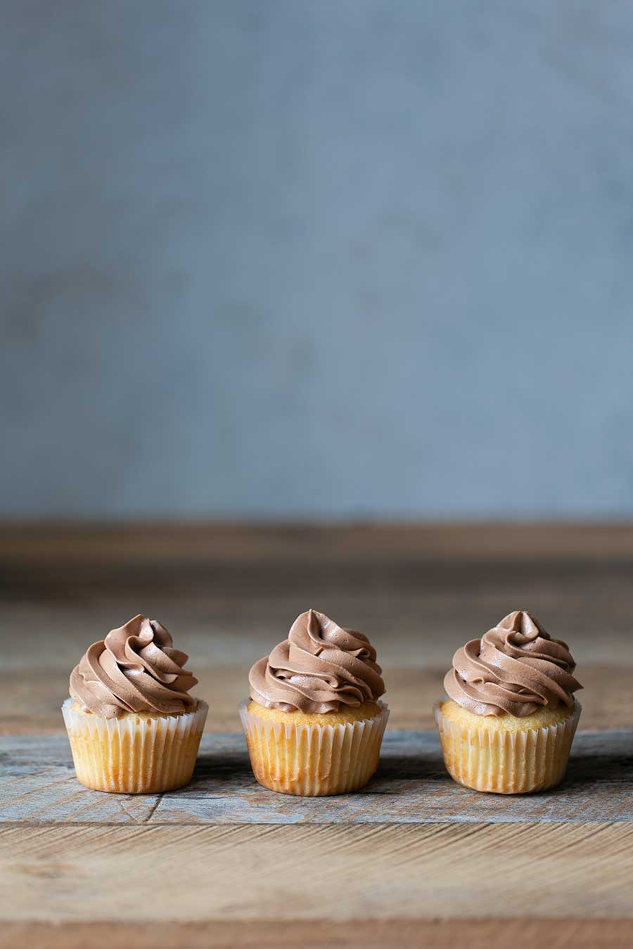 Three vanilla cupcakes with chocolate buttercream