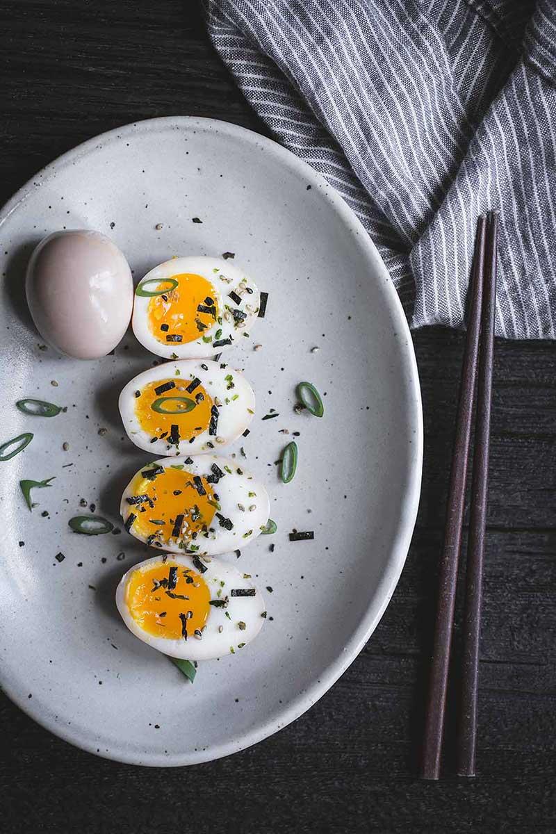 Ramen eggs on a plate with chopsticks