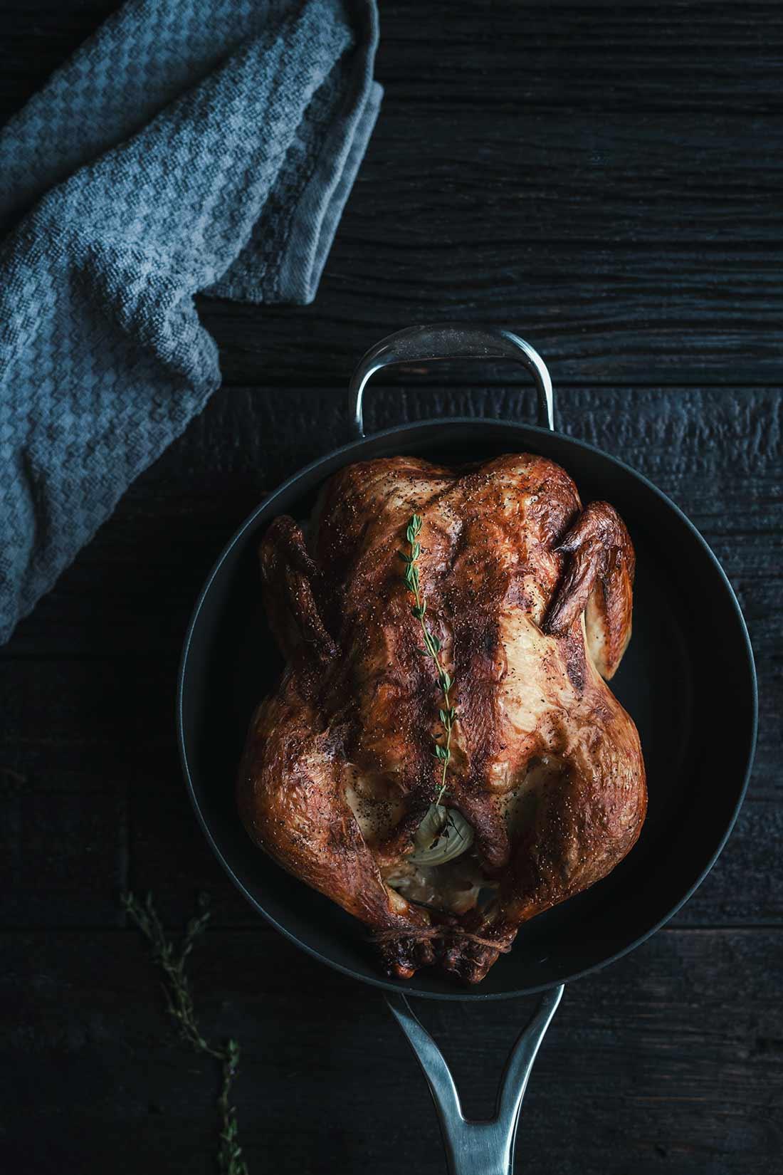 Buttermilk chicken in pan with blue towel in upper left corner