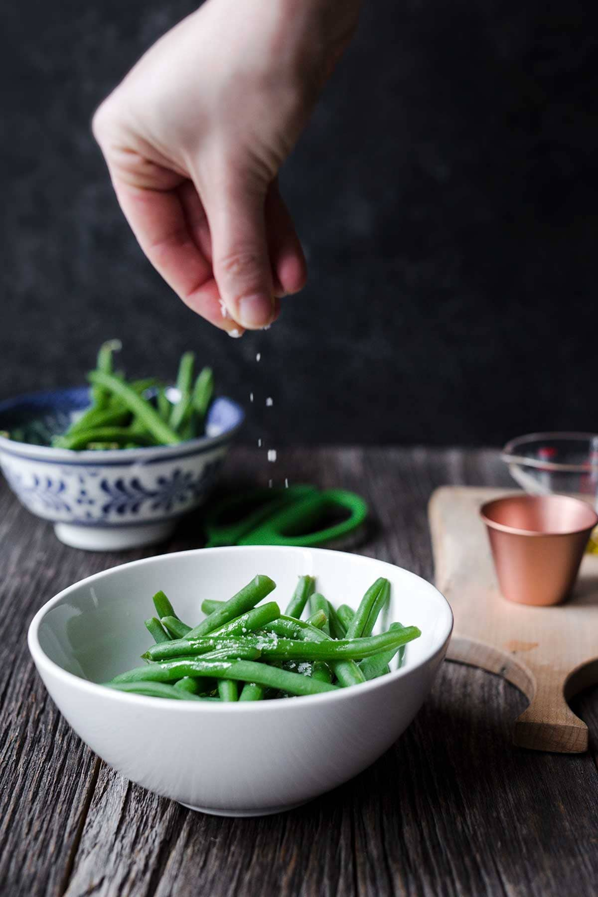 Sprinkling salt over green beans