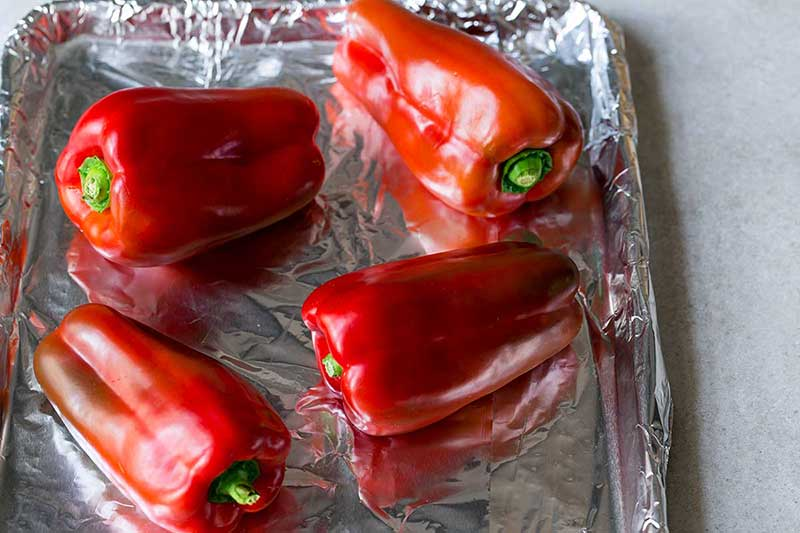 Red bell peppers on foil-lined sheet pan