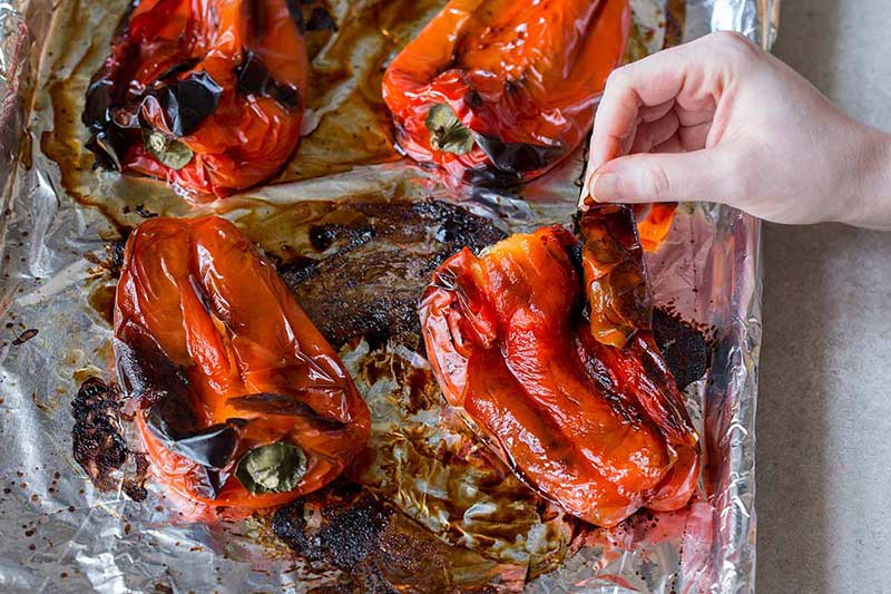 A hand peeling roasted red peppers
