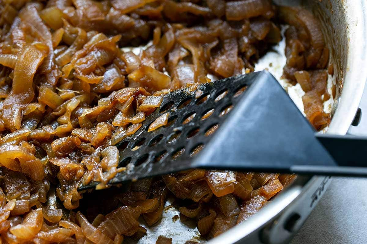 Using spatula to cook onions