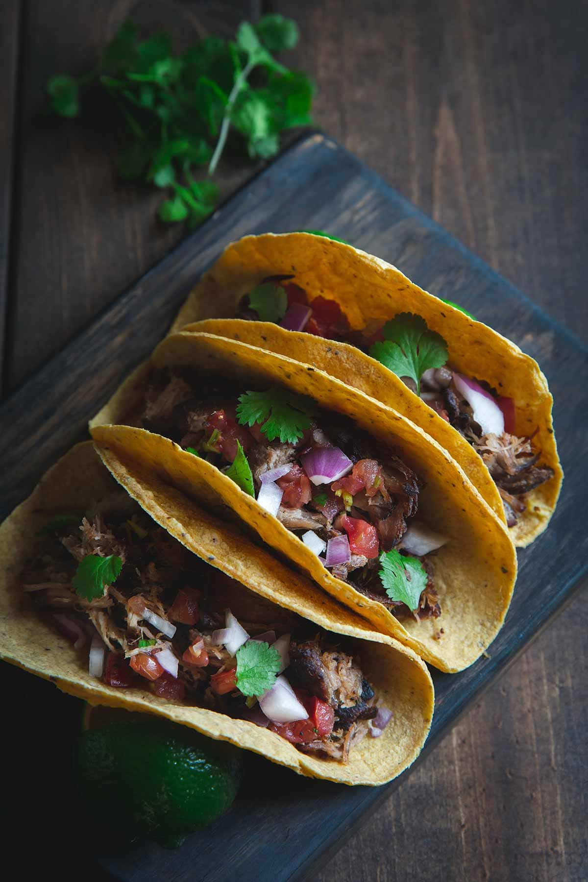 Three pork carnitas tacos lined up on a cutting board