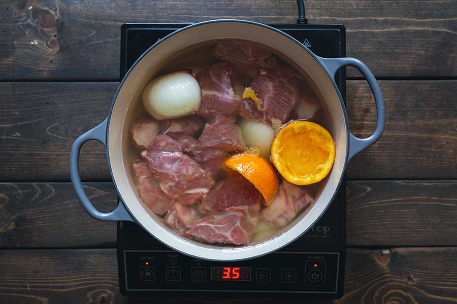 Pork, onions, orange, and other ingredients in melted lard