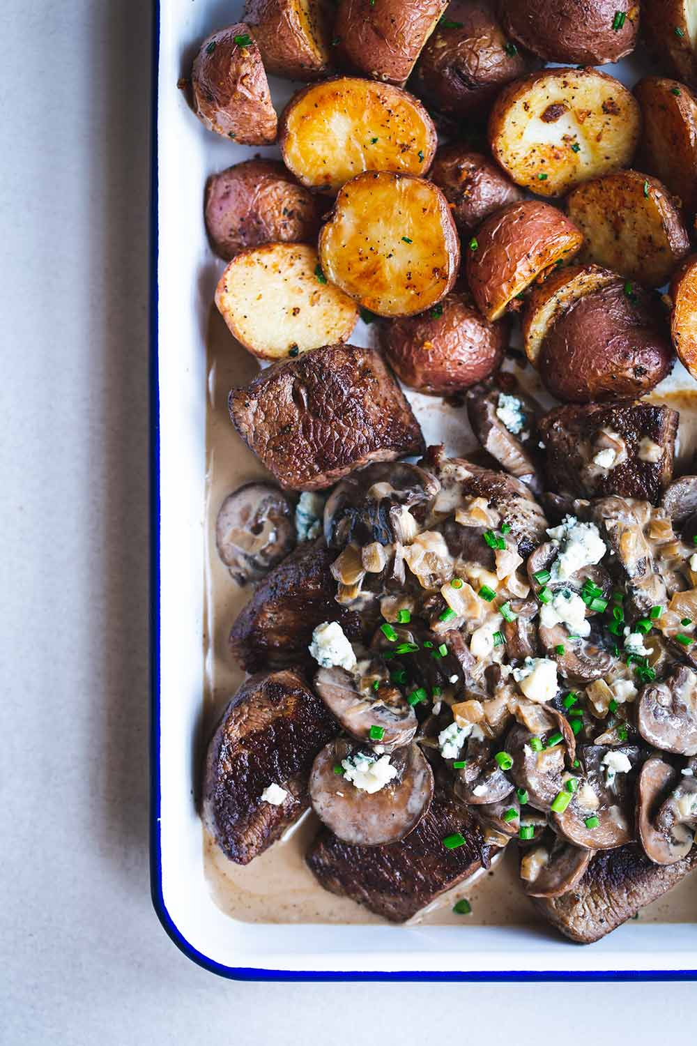 Steak tips, mushrooms, blue cheese sauce and potatoes on a sheet pan