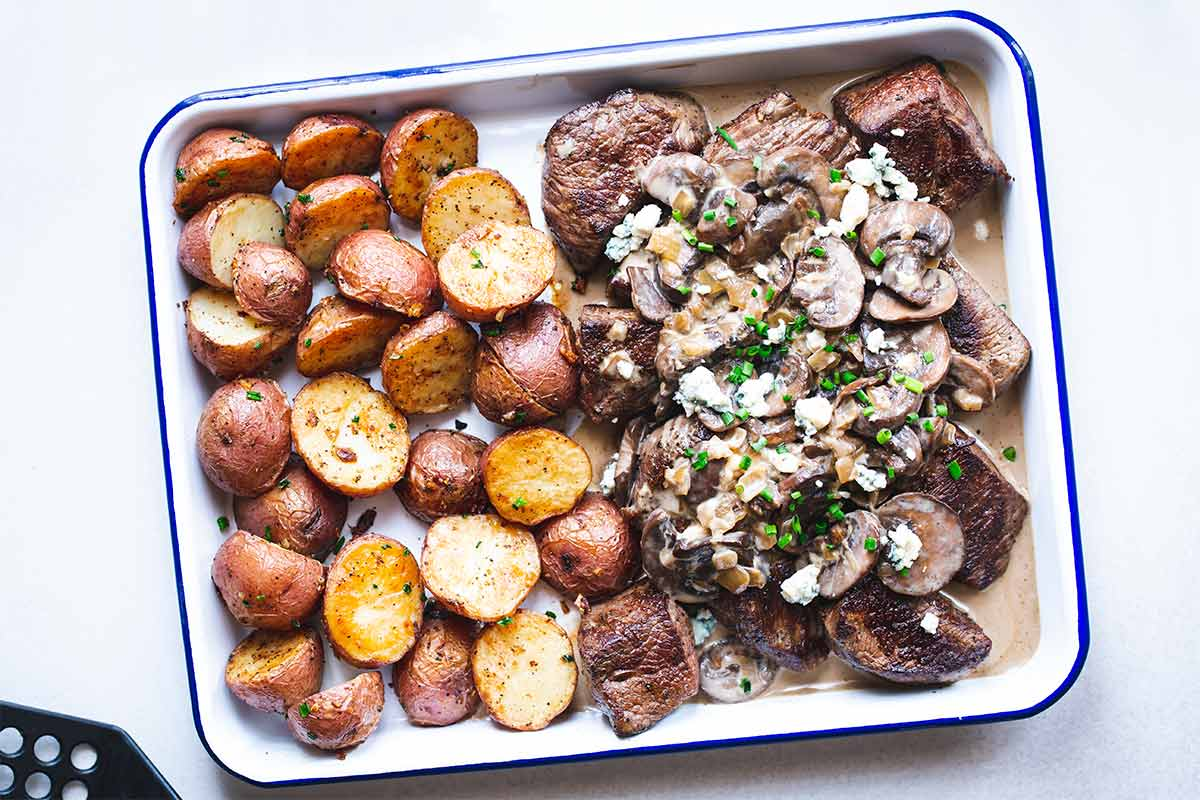 Steak tips recipe with mushrooms, blue cheese sauce and potatoes on a sheet pan, shot from overhead