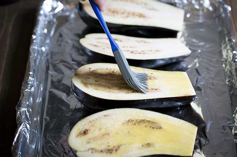brushing olive oil onto eggplant that's been sliced in half.