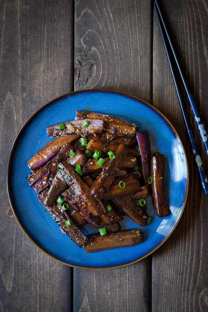 Chinese eggplant recipe on a blue dish with chopsticks