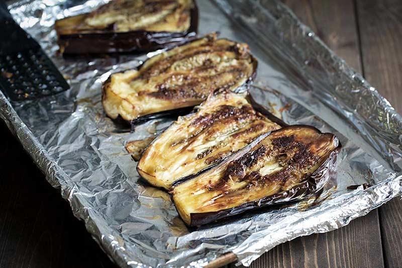 Roasted eggplant in a pan, flipped over to show pulp side