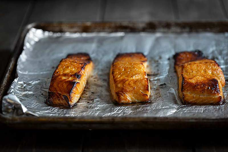 baked salmon on a sheet pan lined with foil